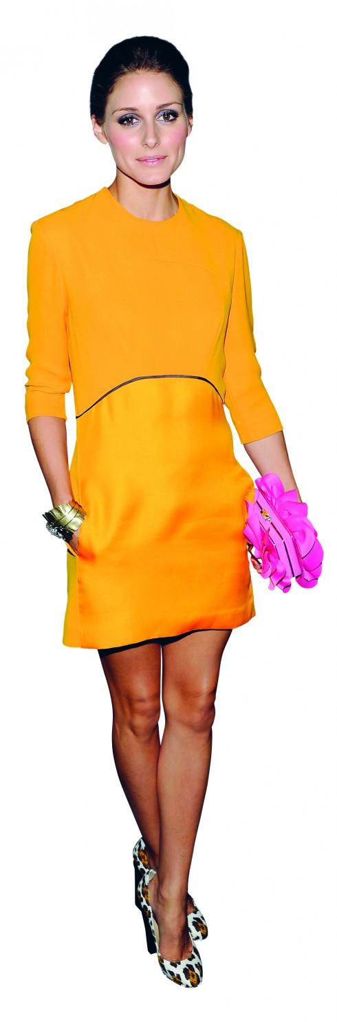 <b>4.</b> Olivia hiện đại và tinh tế trong chiếc đầm vàng cam đơn giản của VICTORIA BECKHAM kết hợp với clutch hồng nổi bật.