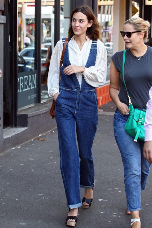 Alexa dạo phố với phong cách vintage pha chút boho khi kết hợp quần yếm denim và áo sơmi trắng đi kèm với túi xách da nâu và sandals đế xuồng.
