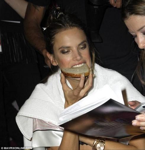 Người đẹp Alessandra tranh thủ ăn một lát bánh mì trong khi chuẩn bị cho show diễn.