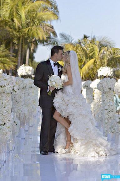 Nữ diễn viên Joanna Krupa của phim truyền hình Real Housewives of Miami mang đến cho bạn cảm hứng rất khác lạ với chiếc đầm cưới. Vừa gợi cảm lại rất ấn tượng và không kém phần kiêu sa, đó là kiểu đầm high-low có phần đuôi dài bồng bềnh như những cánh hoa đua nở.