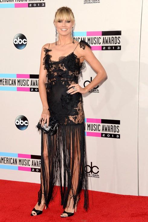 Heidi Klum chọn váy chân tua rua Marchesa, hoa tai dáng dài Lorraine Schwartz, clutch và giày cùng tông màu đen.