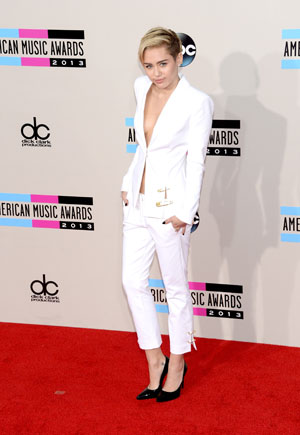 Miley Cyrus xuất hiện trong bộ suit trắng khiêu khích người nhìn, đi cùng giày đen tuyền.<br/>LOS ANGELES, CA - NOVEMBER 24:  Singer Miley Cyrus attends the 2013 American Music Awards at Nokia Theatre L.A. Live on November 24, 2013 in Los Angeles, California.  (Photo by Jason Kempin/Getty Images)