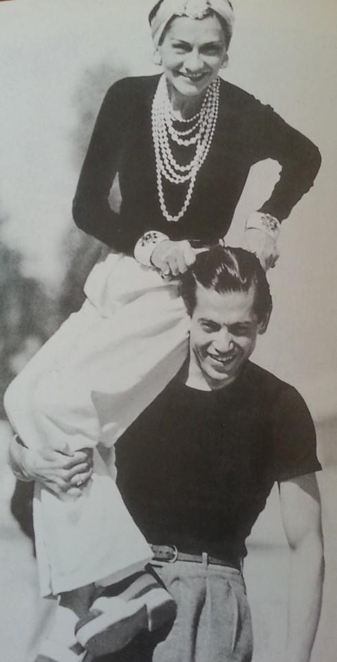 Coco Chanel cùng một người bạn. Bà mặc quần trắng và quấn khăn trên đầu, đeo chuỗi ngọc trai sau này trở thành huyền thoại.