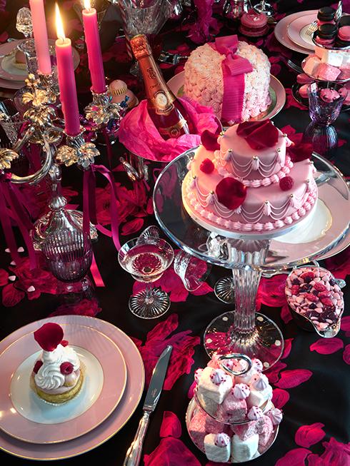 """Nếu không muốn lựa chọn phong cách thôn dã, muốn thể hiện chút """"girly"""" của một người phụ nữ ngọt ngào nơi thành thị, thì có lẽ bạn nên thử chọn màu hồng thay cho màu đỏ truyền thống của Giáng sinh. Sự lung linh của bàn tiệc đến từ những chân nến bằng bạc, bộ đồ ăn cao cấp và những chiếc ly được thiết kế theo đúng mẫu truyền thống. Đừng quên rằng với một không khí tiệc tùng thì """"more is always more"""". Bàn tiệc do giám đốc sáng tạo của Lanvin, Alber Elbaz lên ý tưởng sáng tạo."""