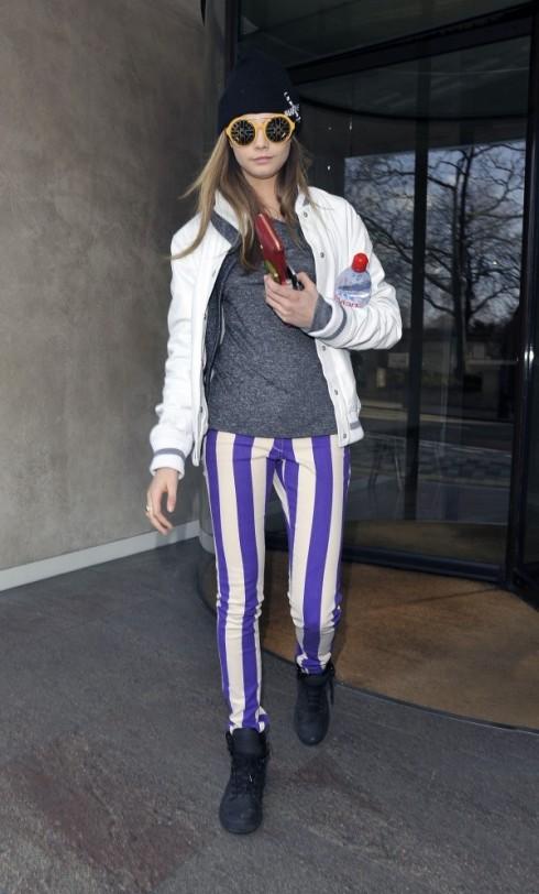 Cara bước ra từ khách sạn tại Paris. Cô diện đồ đơn giản với tank top xám mặc bên trong áo bomber bo tay trắng, điểm nhấn là chiếc quần sọc nổi bật.