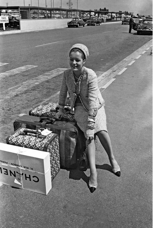 Trái ngược với những chiếc áo khoác chít eo của Dior vào thời điểm đó, chiếc áo vải tweed có phom dáng chắc chắn, cho phép phụ nữ thoải mái di chuyển nhanh chóng trở nên thịnh hành vào những năm 1950 – thời điểm đánh dấu sự chuyển mình trong vai trò của nữ giới trong xã hội. <br/>Trong hình là minh tinh điện ảnh Romy Schneider duyên dáng trong chiếc áo khoác vải tweed tại sân bay Orly.