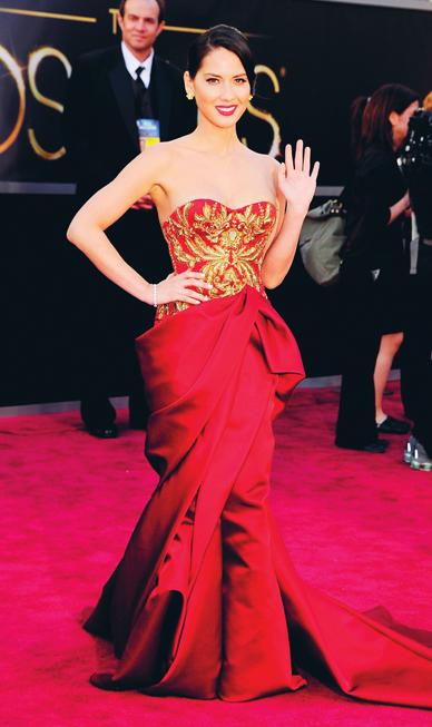 Tại Oscar 2013, Olivia Munn trông vô cùng vương giả trong chiếc đầm satin đỏ có những chi tiết thêu ánh vàng của Marchesa.
