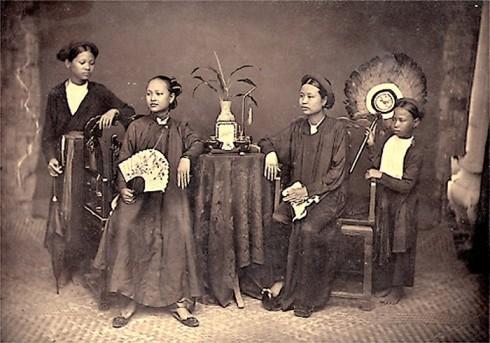 Ảnh cho thấy sự phân biệt tầng lớp trong một gia đình, chủ mặc áo ngũ thân, người hầu mặc áo tứ thân (1884-1885)