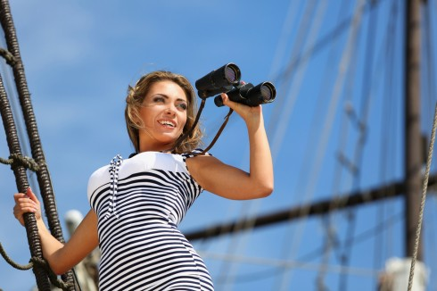 Girl with binoculars standing on the ship, and looks into the di