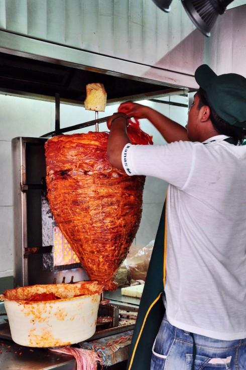 Từng lát thịt heo mỏng tẩm gia vị được đắp lên, làm thành cây Al Pastor.