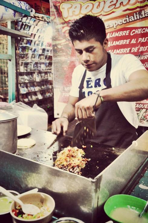 Bạn đầu bếp trẻ ở góc chợ thành phố Oaxaca đang làm nóng thịt Al Pastor.