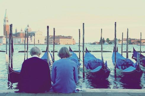 Hai bà lão ngồi đọc sách dưới ánh chiều ở bến tàu San Marco.