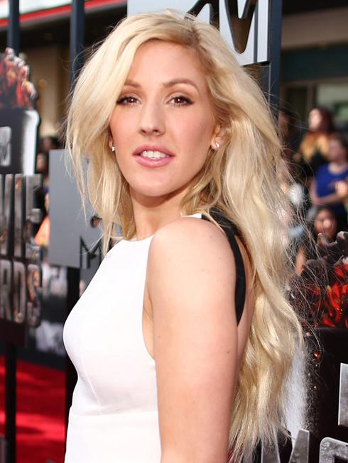 Để phù hợp với chiếc đầm trắng, Ellie chọn phong cách trang điểm tự nhiên: Môi phớt hồng điểm chút son bóng, phấn mắt màu nâu nhạt và đường kẻ mắt đậm làm điểm nhấn duy nhất. Mái tóc vàng rực rỡ, vốn là dấu ấn đặc trưng của Ellie, được cô uốn dợn sóng và buông dài tự nhiên.