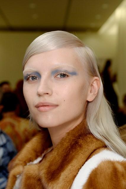 Prada Xuân Hè 2014<br/>Pat McGrath luôn là người đầu tiên thể nghiệm những kỹ thuật làm đẹp mới. Vì thế chẳng mấy ai ngạc nhiên khi thấy súng bắn sơn trang điểm mi mắt cho các người mẫu  Prada. Từ màu xanh oliu  đến xanh dầu,  tất cả các màu phối hợp hoàn hảo với những thiết kế của Miucia Prada.