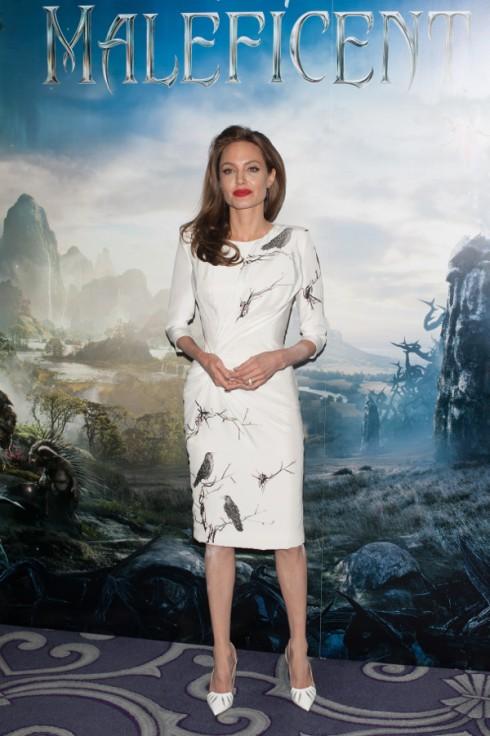 Ngày 9/5, Angelina Jolie quyến rũ trong buổi ra mắt phim 'Maleficient' tại London  với chiếc đầm cocktail trắng của Atelier Versace và môi son đỏ quuyền lực.<br/>Điểm nhấn nút xoắn bên hông giúp khéo léo khoe đường cong. Hình vẽ con quạ rất phù hợp cho bối cảnh rừng rú bí ẩn và nhân vật phù thủy của bộ phim.