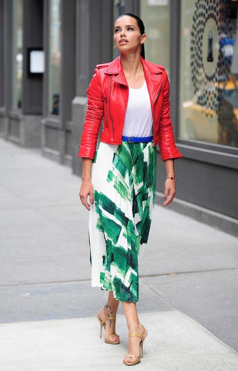 Adriana Lima <br/>Adriana Lima mix & match theo xu hướng color block với áo khoác màu đỏ nổi bật, áo phông trắng, chân váy maxi và thắt lưng xanh cobalt.