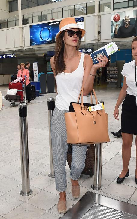 Alessandra Ambrosio<br/>Alessandra xuất hiện tại sân bay với phong cách đơn giản và thoải mái. Cô mặc áo sát nách màu trắng trơn, quần sọc và đôi giày espadrilles da lộn.