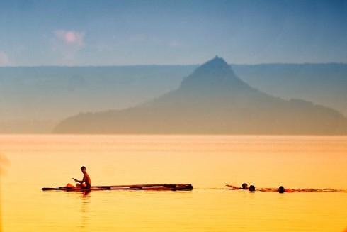Vào hạ (Trẻ em chơi đùa, bơi lội vào buổi chiều trong lòng hồ núi lửa Taal, Philippines).Tác giả Nguyễn Việt Hùng
