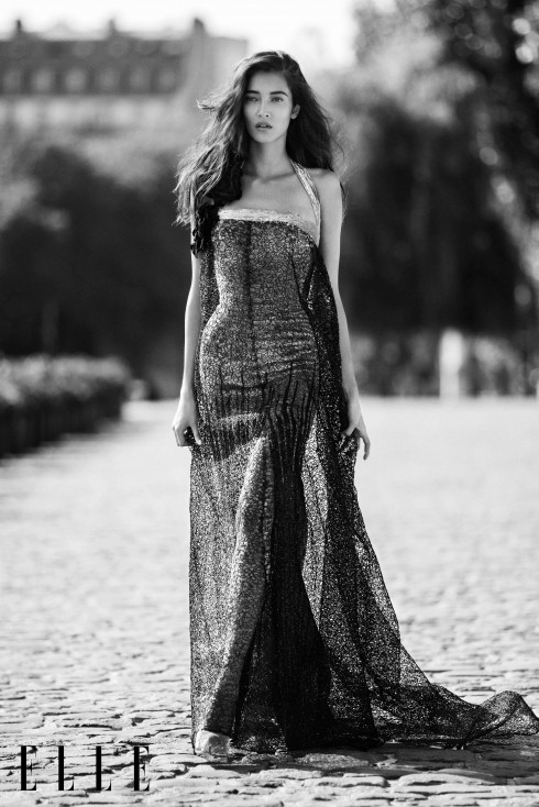 Georges Chakra<br/>Đầm dài chất liệu óng ánh với lớp bên ngoài đục lỗ làm bằng raffia (sợi cọ) màu xanh dương.