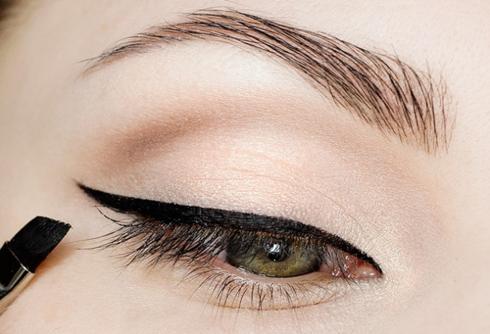 Tán phấn màu nâu đậm ở đuôi mắt để tạo chiều sâu. <br /> Kẻ một đường viền mắt đen đậm bằng gel.