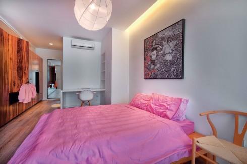 Tủ quần áo và kệ tivi được tích hợp làm cho không gian buồng ngủ rộng rãi hơn. Nhờ vậy, tại đây có thể kê thêm bàn làm việc và giá sách được thiết kế phù hợp tỷ lệ của không gian.