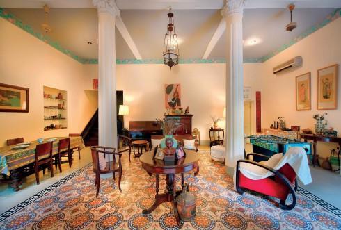 Ngôi nhà giữ nguyên phong cách Đông Dương xưa với cửa gỗ sơn xanh, sàn gạch vẽ tay, những cột chống nhà cũng như các bức tranh từ những năm 1940.