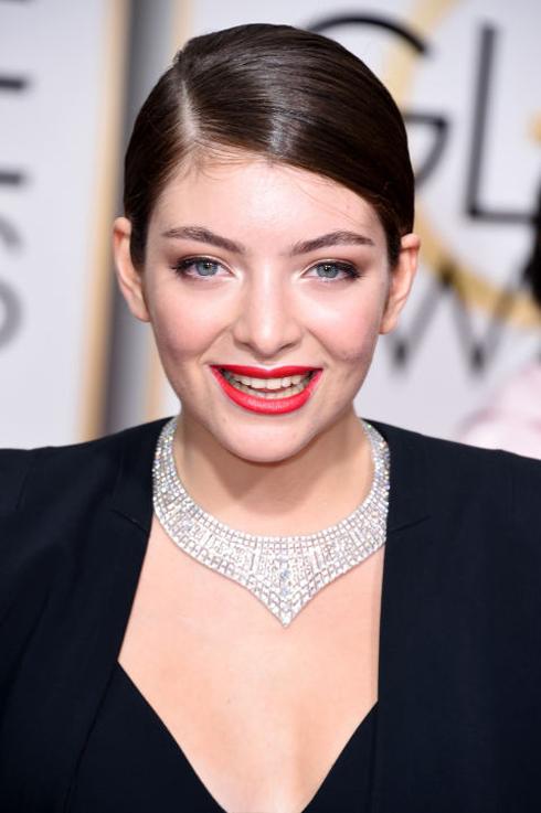 <strong>Lorde</strong> <br> Cô trông thật khác lạ khi trang điểm dịu nhẹ, môi son đỏ cam tươi thắm và tóc đuôi ngựa bóng mượt, so với phong cách