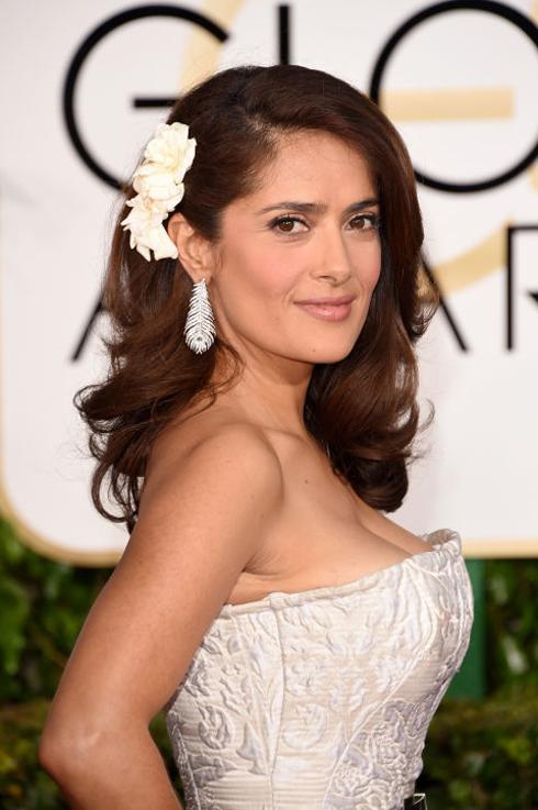 <strong>Salma Hayek</strong> <br> Ít khi ta thấy được bóng dáng những bông hoa đồng nội giản dị cài tóc trên thảm đỏ, Salma thật đáng yêu với đầm và hoa tai trắng tông xuỵt tông cùng kiểu trang điểm tối giản.
