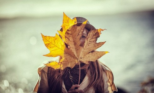 Girl holding giant leaf over face