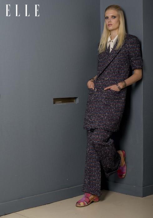 Chanel<br/>Áo khoác chất liệu fantasy tweed, áo top chất liệu jersey, quần chất liệu fantasy tweed, vòng đeo tay bằng vàng và bạc, bốt chất liệu da bê lộn in họa tiết.