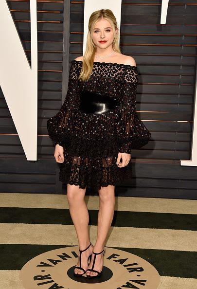 Chloe Grace Moretz diện chiếc váy để lộ bờ vai tròn trịa. Bộ váy này nằm trong BST McQueen Pre thu đông 2015 với các họa tiết trong suốt in trên váy và thắt lưng ngang eo bóng bẩy. Moretz đến dự Vanity Fair Oscar Party tại Los Angeles ngày 22/02/2015