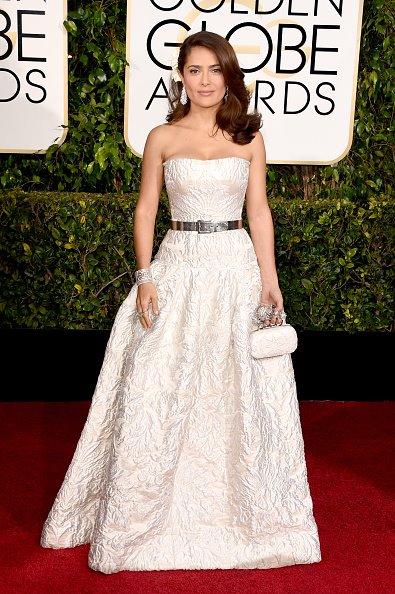 Salma Hayek Pinault lộng lẫy trong chiếc váy trắng in hoạt tiết nổi cùng clutch tông xuyệt tông đến dự Golden Globes lần thứ 72 ngày 11/2.