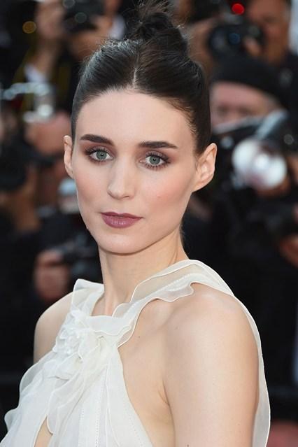 Rooney Mara chọn tông màu trầm cho mắt và môi. Mái tóc búi cao giúp người đẹp trông thật tinh tế.