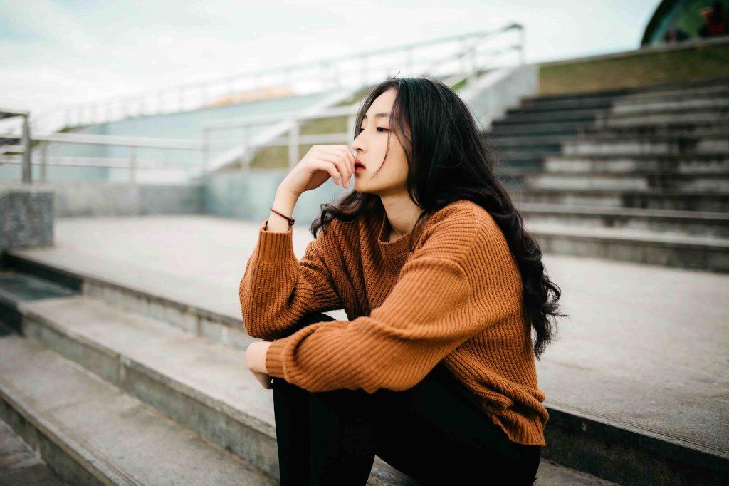 cô gái mặc áo len màu cam mệt mỏi