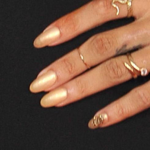 Bộ móng màu gold với kí hiệu dollar bằng vàng ở ngón út của Rihanna khi cô tham dự buổi trao giải Grammy lần thứ 54 ở trung tập Staples tại Los Angeles, CA ngày 12 tháng 2,2012.