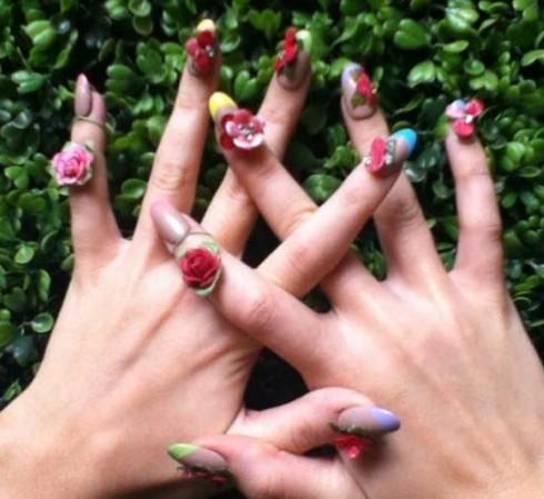 """Thay vì vẽ hình trực tiếp lên móng, Katy Perry đã biến bàn tay của mình thành một """"vườn hoa"""" nhỏ với những bông hồng làm từ đắt sét khô được đính trên bộ móng trong suốt với phần viền của những gam màu lạnh"""