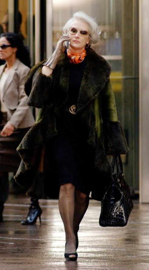 Áo khoác Dennis Basso, bên trong đầm Donna Karan, thắt lưng Cavalli. Điểm nhấn với phụ kiện gồm mắt kính Versace, Túi Fendi và giầy cao gót của Hermes