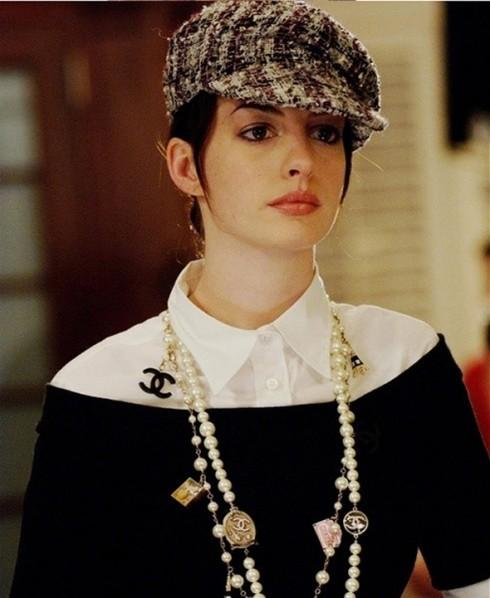 Áo chemise trắng của Miu Miu được phối với áo cổ thuyền màu đen của David Rodriguez, đi kèm dây chuỗi dài hạt ngọc trai và mũ beret của Chanel.
