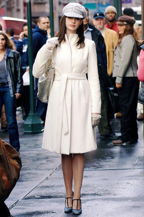 Nữ diễn viên Anne Hathaway thật nữ tính với gam trắng tinh tế gồm giầy cao gót của Marni, áo khoác ngoài Ivory Angora, nón và găng tay của Chanel. Túi dạng boho của Calvin Klein Gold Python.