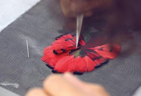 Người thợ thủ công nhà Lemarié tỉ mỉ gắn từng chiếc lông vũ lên nhau để mang đến một tác phẩm hoàn mỹ.