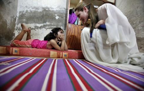 Cô vui vẻ trò chuyện với một bé gái người Iraq đang tị nạn tại Jaramana, ngoại vi phía nam thành phố Damascus, Syri.
