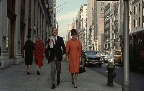 Holly như một viên kẹo ngọt ngào nổi bậc trên phố trong chiếc áo khoác khuy đúp ngực (double-breasted coat) dáng dài, bằng len sợi cao cấp màu cam sánh bước đẹp đôi bên chàng nhà văn lãng tử Paul Varjak.