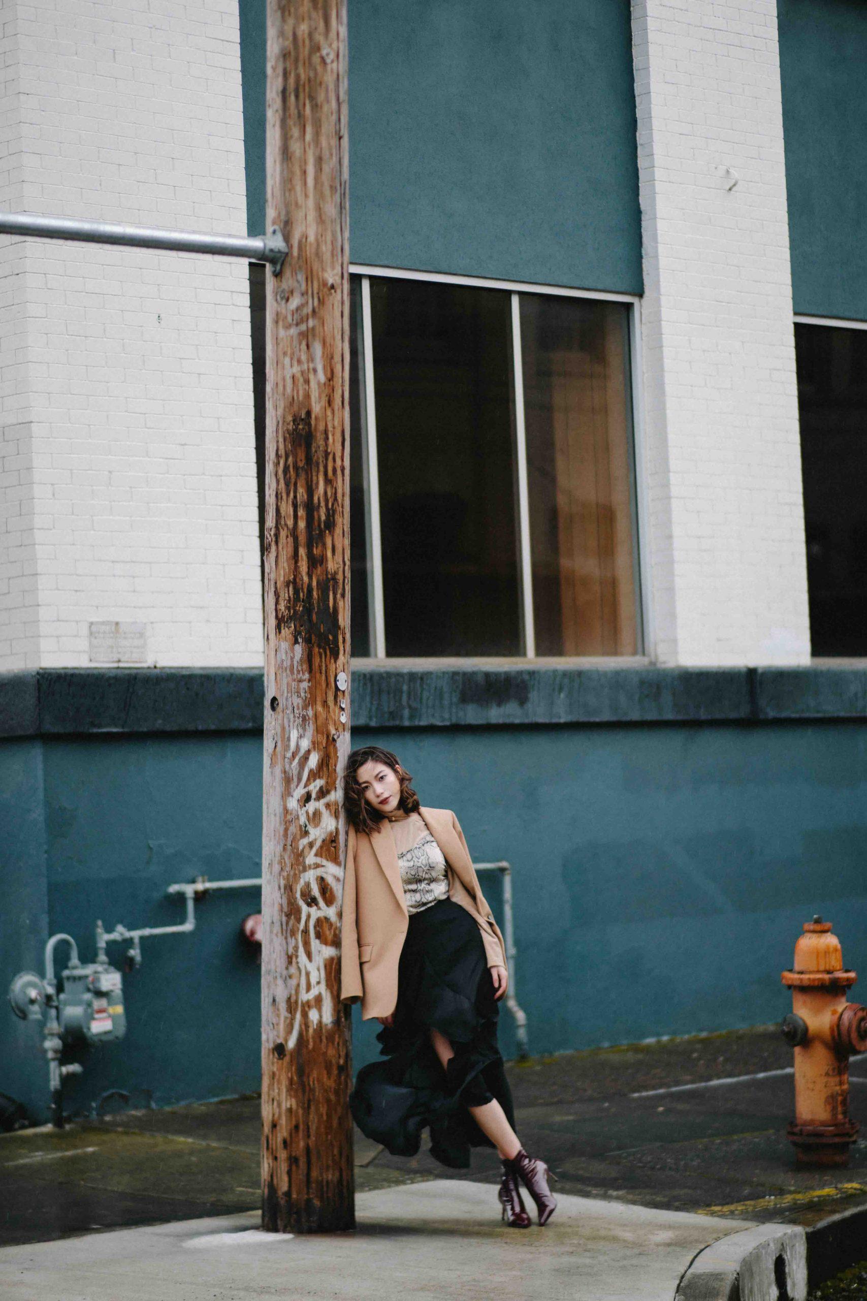 cô gái cung hoàng đạo đứng cạnh cây cột