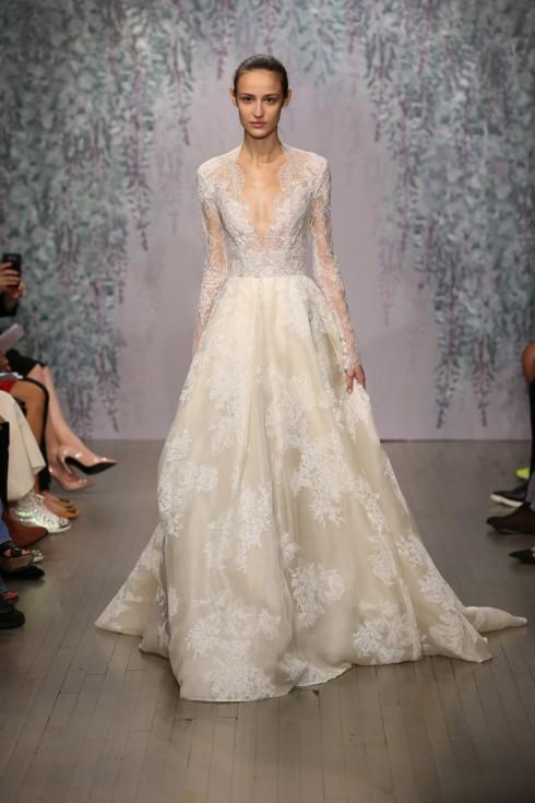 Cổ điển như một cô dâu hoàng gia với tay áo đắp ren, eo thon và ren đính khéo léo.