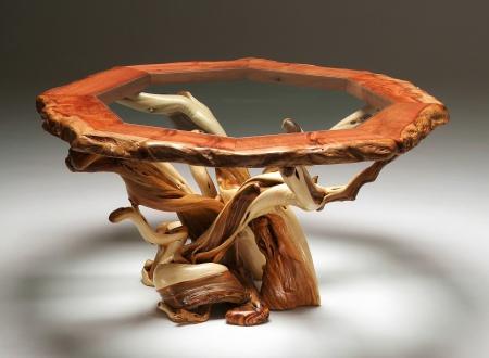 Bàn ăn làm từ gỗ đỏ kết hớp với mặt kính. Chân đế là những nhánh cây nguyên bản được tạo hình đầy nghệ thuật.