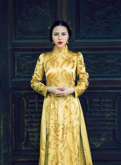 Không hẳn là gấm nhưng kiểu dáng cổ điển với tay phồng, cổ áo cao cùng màu vàng hoàng hậu cũng là một lựa chọn khéo léo. (Áo dài Văn Thành Công)