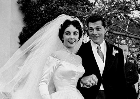 Nữ diễn viên Elizabeth Taylor mặc váy cưới làm bằng satin (trị giá 1,500USD - món quà từ hãng phim MGM) nắm tay cùng chồng là Nicky Hilton .