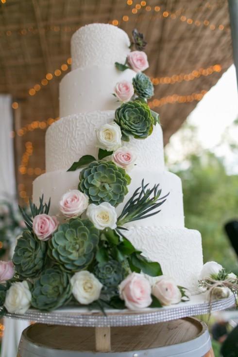 Bánh cưới trắng tinh khiết trở nên nổi bật và ấn tượng với những bông hoa sứ xanh lạ mắt.