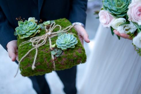 Gối nhẫn độc đáo được làm từ thảm rêu và hoa đá, tượng trưng cho sự trường tồn của tình yêu đôi lứa.
