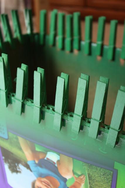 Bước 1: cố định kẹp gỗ vào thùng giấy, dùng sơn xịt phủ màu lên các cây kẹp và đợi khô.